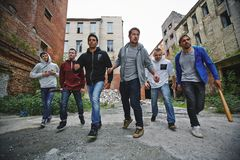 Malicious guys. Group of spiteful hooligans walking along grunge brick houses Royalty Free Stock Image
