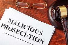 Malicious prosecution and gavel on a table. Malicious prosecution, documents and gavel on a table in a court Royalty Free Stock Photography