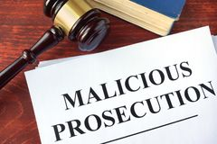 Malicious prosecution  and gavel. Malicious prosecution  and gavel on a table Stock Image