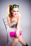 Malicious smile. Young woman in plastic dress and heavy make up with malicious smile studio shot Royalty Free Stock Images