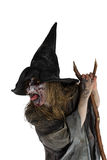 Malicious Witch. Witch is leaning on her broom and sticks her tongue out Royalty Free Stock Images