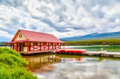 Maligne Lake in Jasper National Park in Alberta Canada. Colorful canoes lie on the boat house dock at Maligne Lake in Jasper National Park, Alberta, Canada. The Royalty Free Stock Image