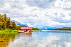 Maligne Lake in Jasper National Park in Alberta Canada. Colorful canoes lie on the boat house dock at Maligne Lake in Jasper National Park, Alberta, Canada. The Royalty Free Stock Photo