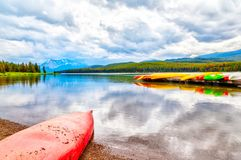 Maligne Lake in Jasper National Park in Alberta Canada. Colorful canoes lie on the dock at Maligne Lake in Jasper National Park, Alberta, Canada. The lake is Stock Images