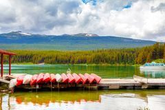 Maligne Lake in Jasper National Park in Alberta Canada. Colorful canoes lie on the dock at Maligne Lake in Jasper National Park, Alberta, Canada. The lake is Royalty Free Stock Photo