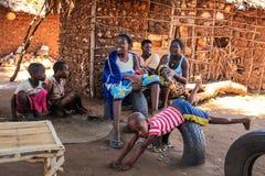Malindi, Kenia - 6. April 2015: Lokale Frauen mit ihren Kindern, die vor ihrem provisorischen Haus sitzen Trotz der Armen stockbild