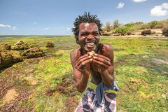Local beach boy posing for tourists holding small crab. Malindi, Kenya - April 08, 2015: Local beach boy posing for tourists holding small crab and smiling Stock Photos