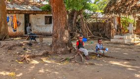 Malindi, Kenya - April 06, 2015: Unknown local kids sitting on tree root in front of their house. Living conditions in this area. Are generally poor royalty free stock photos