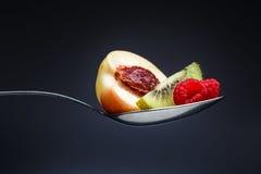 Malinki, brzoskwinia i kiwi na wyginającej się łyżce, Obraz Royalty Free