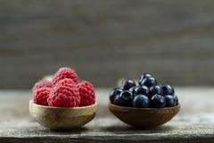 Malinki i czarne jagody w łyżkach na drewnianym tle zdrowe jeść zdjęcia stock