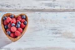 Malinki i czarne jagody w drewnianym sercowatym naczyniu obraz stock