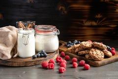 Malinki w przedpolu, mleku i ciastkach w backround, fotografia royalty free