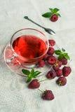 Malinowa herbata w szklanej filiżance obraz stock