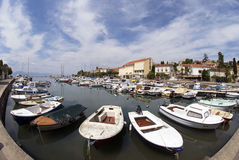 Malinska harbour on the island Krk in Croatia. Horizontal photo of port of Malinska on the island Krk with fisherman's and motor boats,houses and blue sky in Stock Photo