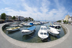 Malinska harbour on the island Krk in Croatia. Horizontal photo of port of Malinska on the island Krk with fisherman's and motor boats,houses and blue sky in Stock Image