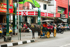 Malioboro, main street in Yogjakarta. YOGYAKARTA, INDONESIA - SEPTEMBER, 13: Main street in Yogjakrata full of local traffic - horses, rickshaws, carriages Stock Image