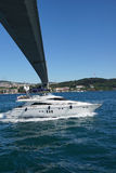 Mall boat cruises  under Bosphorus Bridge. ISTANBUL - MAY 18, 2014 - Small boat cruises  under Bosphorus Bridge  in Istanbul, Turkey Stock Photo
