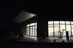 Mall Closed. The darkened facade of a mall after hours with a single shopping cart in silhouette Royalty Free Stock Images