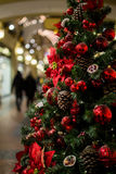 Mall with decorated Christmas pine. Cones, flowers and red balls Stock Photo