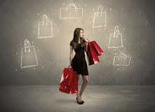 Mall lady with drawn shopping bags on wall Stock Photos