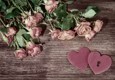 Mall pink garden roses and hearts on wooden surface. Retro style romantic floral background. Valentines day background. Love Stock Image