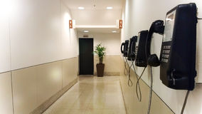 Mall public phones corridor. A lot of black phone in a mall corridor. Mall public phones corridor. A lot of black phones in a mall corridor with lights Royalty Free Stock Images