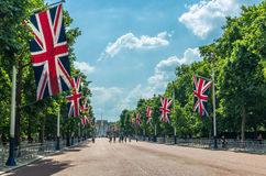 Union Jack flags and tourists on the Mall in London. The Mall is a road in the City of Westminster, central London, between Buckingham Palace at its western end Stock Photos
