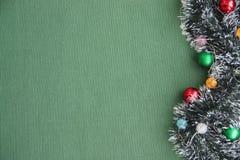 Malla del ` s del Año Nuevo, guirnalda, bolas en un fondo verde Lugar para la inscripción Imagen de archivo libre de regalías