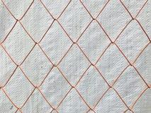 Malla metálica anaranjada con la hoja plástica blanca en fondo Fotos de archivo libres de regalías