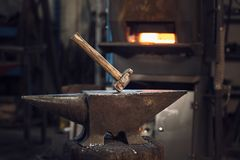 Mallet on an anvil in front of a furnace. Mallet on an anvil in front of a red hot burning furnace in a metalworking workshop or blacksmith stock image
