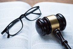 Mallet And Eyeglasses On Open Legal Book. High angle view of mallet and eyeglasses on open legal book in courtroom Royalty Free Stock Photo