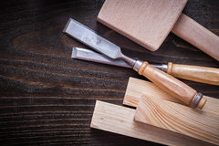 Mallet firmer chisels and wooden planks on brown Stock Photo