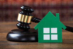 Mallet With Green Paper House In Courtroom. Closeup of wooden mallet with green paper house on table in courtroom stock photos