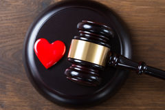 Mallet And Heart On Table In Courtroom. High angle view of mallet and heart on table in courtroom Stock Photo