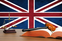 Mallet, legal code and scales of justice. Mallet, legal code and scales of justice with the United Kingdom union jack flag behind Stock Image