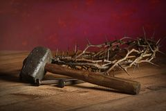 Mallet, Nails and Crown of Thorns. Mallet, crown of thorns and large nails on wooden table over red background royalty free stock photography
