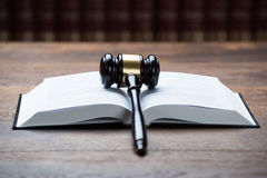 Mallet On Open Legal Book In Courtroom. Closeup of mallet on open legal book at table in courtroom Royalty Free Stock Images