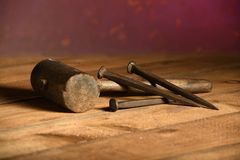 Mallet and Three Metal Spikes. Mallet and three large metal nails over vintage table royalty free stock photography