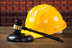 Mallet And Yellow Hardhat In Courtroom. Closeup of wooden mallet and yellow hardhat on table in courtroom Stock Image
