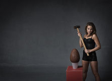 Mallett on chocolate egg. Woman ready to destroying easter egg with big hammer in a dark room Royalty Free Stock Photos
