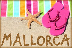 Mallorca beach travel. Concept. MALLORCA written in sand with water next to beach towel and summer sandals and starfish. Spanish vacation holidays concept Stock Photography