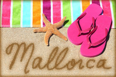 Mallorca beach vacation writing on sand. Mallorca beach travel concept. MALLORCA written in sand with water next to beach towel and summer sandals and starfish Royalty Free Stock Images