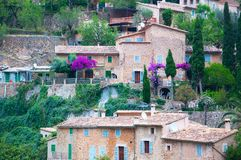 Mallorca Deia village view. With pink bougainvillea, green gardens and traditional and typical honey-colored drystone buildings Royalty Free Stock Images