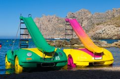 Pedalos parked on Spanish beach. Mallorca, Spain - July 6, 2017: Two brightly coloured pedalos parked on a beach by the water's edge in Cala San Vicente stock photo
