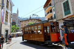 The tram is on street of Soller town and tourists. MALLORCA, SPAIN - JUNE 2: The tram is on street of Soller town and tourists are in outdoor restaurant on June Stock Photo