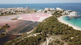 Mallorca spain Paisagem aérea do zangão surpreendente da vila, dos planos cor-de-rosa de sal e da praia encantador Estanys filme