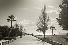 Mallorca spring backlight. PEGUERA, MALLORCA, SPAIN - February 9, 2017: People walk on broad seaside promenade in strong spring backlight on February 9, 2017 in Royalty Free Stock Photo
