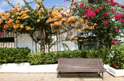 Mallorcan street wiev. Bench surrounded by flowers on a patio Royalty Free Stock Photography