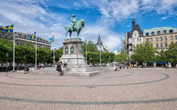 Malmo on a sunny summer day in Sweden. Malmo, Sweden – July 2, 2014: The big square and the statue of King Charles X Gustav in Malmo on a sunny summer day. The Royalty Free Stock Photos
