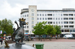 MALMO, SWEDEN - MAY 31, 2107: Gryphon in the center of Malmo in Gustav Adolfs Torg square with trees and a great white building. With clock on the background Royalty Free Stock Photo
